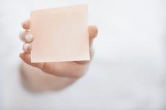 Ludzka ręka trzyma adhezyjną notatkę Obrazy Stock