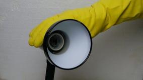 Ludzka ręka w żółtej gumowej rękawiczce odśrubowywa uszkadzającą żarówkę zdjęcie wideo