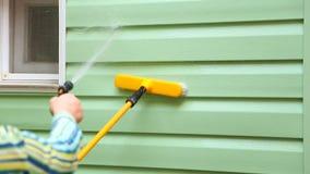 Ludzka ręki domycia I opryskiwania domu ściana zbiory
