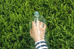 Ludzka ręka w pustej plastikowej butelce Zdjęcia Royalty Free