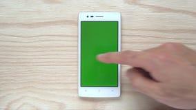 Ludzki obruszenie telefonu komórkowego lub smartphone zieleni ekran na drewnianym tle zbiory wideo