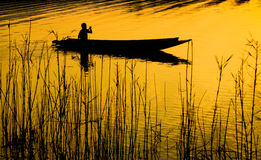Ludzki wioślarstwo na łodzi nad dramatycznym zmierzchem Zdjęcie Stock