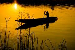 Ludzki wioślarstwo na łodzi nad dramatycznym zmierzchem Fotografia Stock