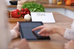 Ludzkie ręki dwa żeńskiego persons używa touchpad dla robić menu w kuchni Zbliżenie dwa kobiety robi online Zdjęcia Stock