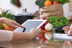 Ludzkie ręki dwa żeńskiego persons używa touchpad dla robić menu w kuchni Zbliżenie dwa kobiety robi online Zdjęcia Royalty Free