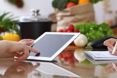Ludzkie ręki dwa żeńskiego persons używa touchpad dla robić menu w kuchni Zbliżenie dwa kobiety robi online Obrazy Royalty Free