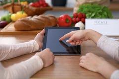 Ludzkie ręki dwa żeńskiego persons używa touchpad dla robić menu w kuchni Zbliżenie dwa kobiety robi online Zdjęcie Stock