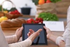 Ludzkie ręki dwa żeńskiego persons używa touchpad w kuchni Zbliżenie dwa kobiety robi online zakupy obok Zdjęcia Stock