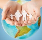 Ludzkie ręki trzyma papierowej rodziny nad ziemską kulą ziemską Obraz Stock