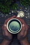 Ludzkie ręki trzymają kubek kawa w którym odbija trochę bitcoin i gałąź świąteczna świerczyna kula ziemska Pojęcie o Zdjęcia Royalty Free