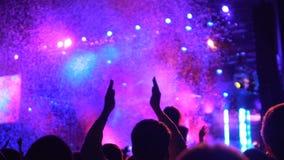 Ludzkie sylwetki oklaskuje, oglądający zadziwiającego kolorowego światło i confetti pokazują zbiory wideo