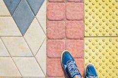 Lue-Turnschuhe auf gelben Tastpflastersteinen Stockfotografie