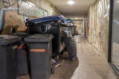 Luebeck, Шлезвиг-Гольштейн, Германия, 17-ое августа 2016, ненужный контейнер и мусорный ящик с спать бродягой на задней части ent Стоковые Фото