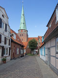 Luebeck Travemuende, narrow lane with church St. Lorenz Stock Photo