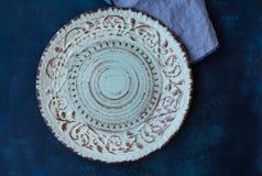 Lueish vintage empty plate, linen napkin on dark blue concrete table top, flat lay, menu template, copyspace Stock Images