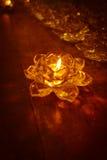 Lueur d'une bougie dans la rosette de plateau sur vieil en bois Images stock