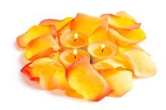 Lueur d'une bougie et pétales de rose dans la couleur orange Photo stock