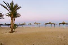 Lueur de coucher du soleil, parasols sur la belle plage sablonneuse Images libres de droits