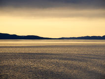 Lueur orange de coucher du soleil au-dessus de l'eau de ondulation Photo libre de droits