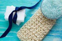 Lufa orgánica del jabón de la sal orgánica natural del mar en una tabla de madera azul Imágenes de archivo libres de regalías