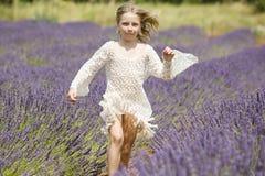 Läufe des jungen Mädchens auf dem purpurroten Lavendelgebiet Lizenzfreie Stockfotos