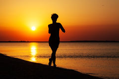 Läufe des jungen Mädchens entlang der Seeküste Stockfotografie