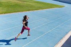 Läufer, der in Richtung zum Erfolg auf Laufbahn sprintet Stockfotos