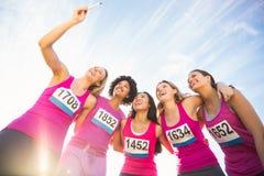 Läufer, die Brustkrebsmarathon stützen und selfies nehmen Stockfotografie