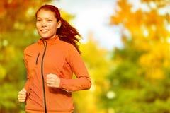 Läuferfrau, die in Fallherbstwald läuft Lizenzfreie Stockfotos