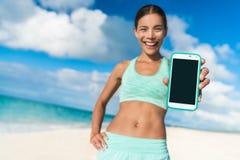 Läuferfrau, die Smartphoneeignungs-APP-Schirm zeigt Stockfotos
