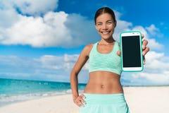 Läufermädchen, das Smartphoneeignungs-APP verwendet Stockbilder