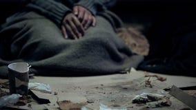 Luffare som täckas med den smutsiga filten som sitter på lådan som bor på gatan, flykting arkivfoto