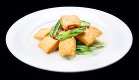 Luffaschwamm kochte den Tofu, chinesische traditionelle Küche lokalisiert auf schwarzem Hintergrund Stockfotografie