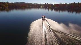 Luft-Ansicht 4k über professionl männlichen Athletenwasserski mit Motorboot im ruhigen Seewasser in der schönen Waldlandschaft