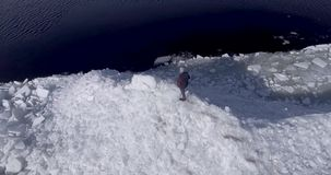 Luft-dron Ansicht des jungen aktiven glücklichen Mannes, der auf den Eisgletschern nahe Küstenlinie von Wintermeer bleibt Brummen stock video