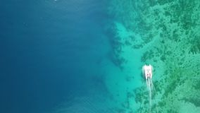Luft-, Spitzenbrummenszene des Katamarans verankert in einer Bucht mit transparentem Türkiswasser und kopierte Unterseite Kamera stock video footage