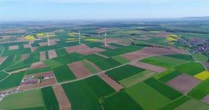 Lufta panoramor av jordbruks- fält och vindgeneratorer producera elektricitet Alternativ energi, tre vindturbiner arkivfilmer