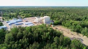 Luftansicht des lauten Summens der kleinen modernen Ziegelstein-Fabrik und des Lagers im Wald im Sommer stock video