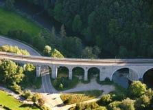 Luftaufnahme: Alte Eisenbahnbrücke, die eine Straße kreuzt Stockfoto