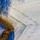 Luftaufnahme eines Feldes mit einer Dünnschicht des Schnees sorgfältig gepflogen in einer geometrisch rechteckigen Form stockbilder