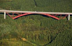 Luftaufnahme: Rote Datenbahnbrücke, die einen Wald kreuzt Lizenzfreie Stockfotografie