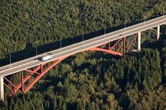 Luftaufnahme: Rote Datenbahnbrücke, die einen Wald kreuzt Lizenzfreie Stockbilder