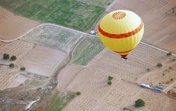Luftballon, der über das Land fliegt Stockfotografie