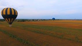 Luftballone, die niedrig über Felder, Dorf am Hintergrund, landwirtschaftliche Energie schwimmen stock video footage