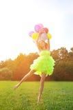 luftballonger samlar ihop den färgrika holdingkvinnan Arkivfoto