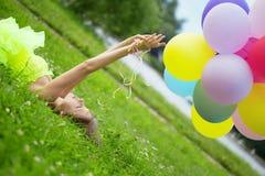 luftballonger samlar ihop den färgrika holdingkvinnan Fotografering för Bildbyråer