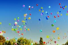 Luftballonger som flyger till ljus blå himmel arkivfoton