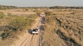 Luftbild einer Wüstensteppenlandschaft mit einem Auto 4x4, das einem kleinen Flussstrom sich nähert lizenzfreies stockfoto