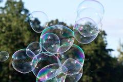 Luftblasen gegen grüne Bäume und Himmel Lizenzfreie Stockbilder