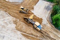 Luftbrummenansicht über den Planierraupen- und Kipper-LKW, der an Baustelle arbeitet stockfotos